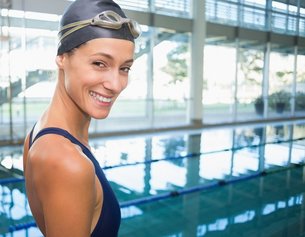 Pretty swimmer smiling at camera by the poolの写真素材 [FYI00002167]