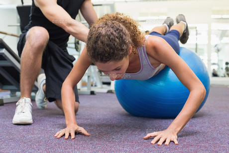 Trainer helping client workout on exercise ballの素材 [FYI00002168]