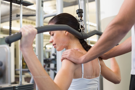 Fit brunette using weights machine for arms with trainer touching shouldersの素材 [FYI00002169]