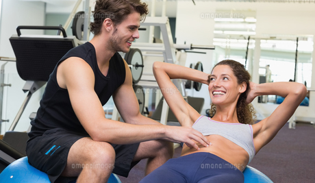 Trainer watching client do sit ups on exercise ballの写真素材 [FYI00002170]
