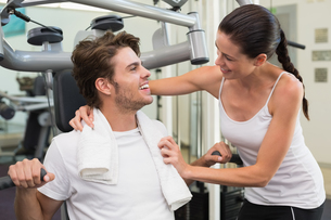 Fit man using weights machine with trainer encouraging himの写真素材 [FYI00002173]