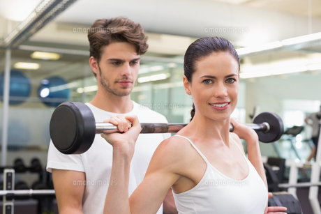 Fit smiling woman lifting barbell with her trainerの写真素材 [FYI00002177]