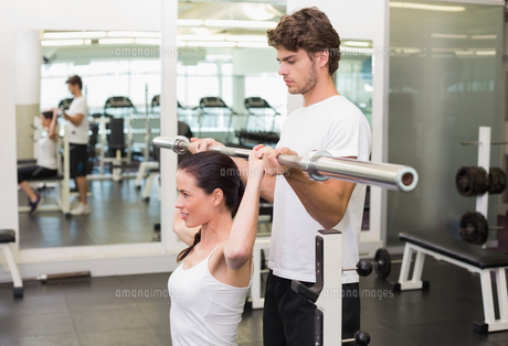 Fit woman lifting barbell with her trainer spottingの写真素材 [FYI00002178]