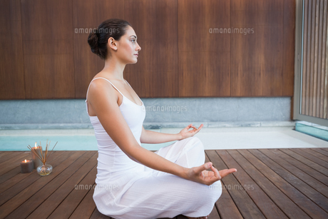Peaceful brunette in white sitting in lotus poseの写真素材 [FYI00002179]