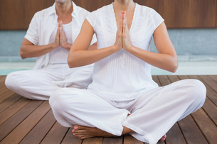 Couple in white sitting in lotus pose with hands togetherの素材 [FYI00002181]