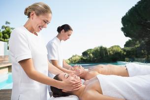 Content couple enjoying head massages poolsideの写真素材 [FYI00002182]