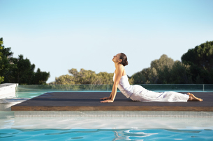 Peaceful brunette in cobra pose poolsideの写真素材 [FYI00002184]