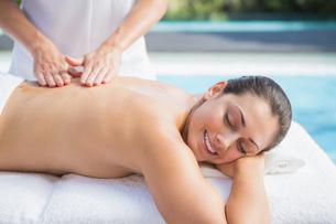 Happy brunette getting a massage poolsideの写真素材 [FYI00002186]