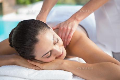 Smiling brunette enjoying a massage poolsideの写真素材 [FYI00002187]