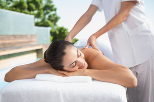 Smiling brunette enjoying a massage poolsideの写真素材 [FYI00002188]