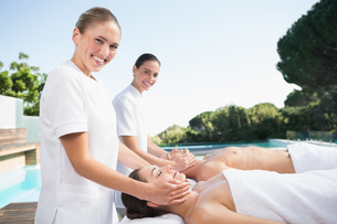 Content couple enjoying head massages poolsideの写真素材 [FYI00002190]