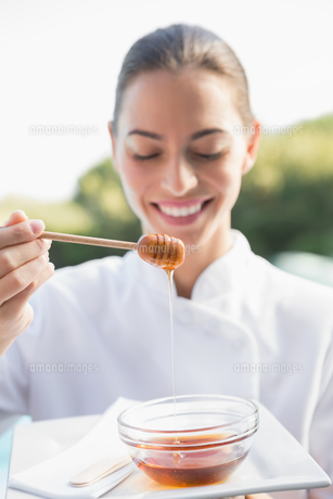 Smiling beauty therapist holding plate with honeyの素材 [FYI00002193]