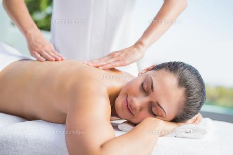 Happy brunette getting a massage poolsideの写真素材 [FYI00002194]