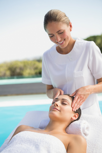 Tranquil brunette getting a head massage poolsideの写真素材 [FYI00002199]