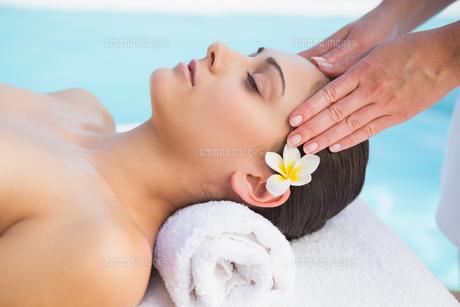 Tranquil brunette getting a head massage poolsideの写真素材 [FYI00002202]