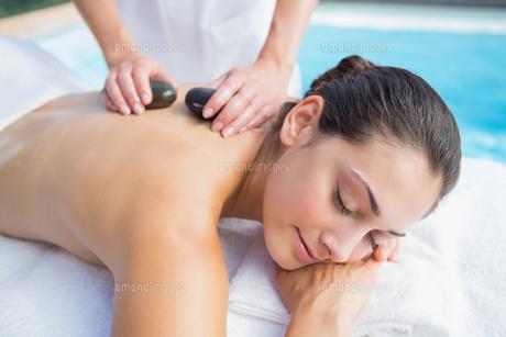 Happy brunette getting a hot stone massage poolsideの写真素材 [FYI00002203]