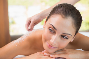 Beauty therapist pouring salt scrub on smiling womans backの素材 [FYI00002204]