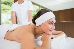 Beauty therapist rubbing smiling womans back with heated mittsの写真素材 [FYI00002206]