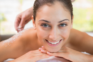 Beauty therapist pouring salt scrub on smiling womans backの素材 [FYI00002208]