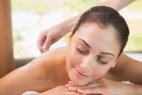 Beauty therapist pouring salt scrub on smiling womans backの素材 [FYI00002209]