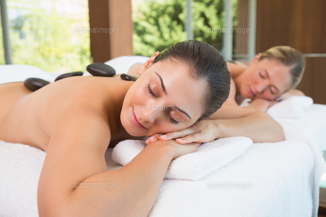 Calm friends lying on massage tables with hot stones on their backsの写真素材 [FYI00002211]