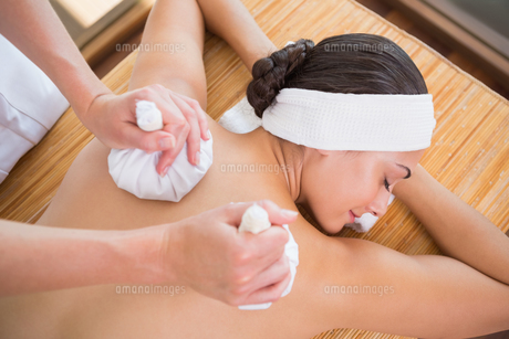 Smiling woman getting a back massage with herbal compressesの素材 [FYI00002213]