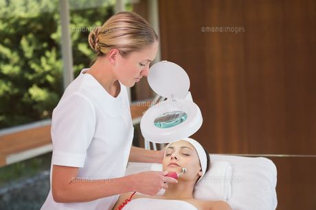Peaceful brunette getting micro dermabrasion from beauty therapistの写真素材 [FYI00002214]