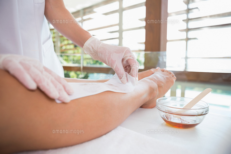 Woman getting her legs waxed by beauty therapistの写真素材 [FYI00002215]