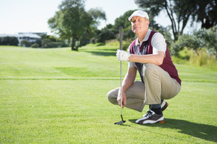 Confident golfer kneeling holding his golf clubの写真素材 [FYI00002220]
