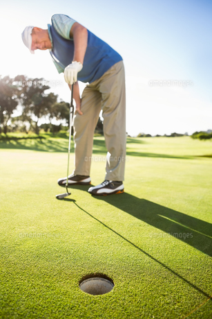 Golfer standing on the putting green watching holeの素材 [FYI00002221]