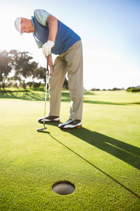 Golfer standing on the putting green watching holeの写真素材 [FYI00002221]