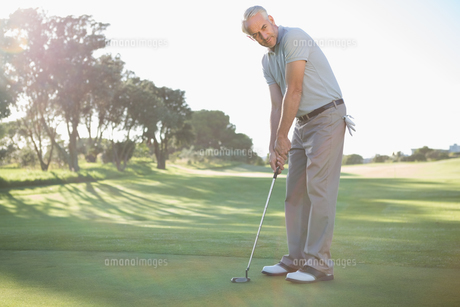 Handsome golfer putting ball on the greenの写真素材 [FYI00002222]
