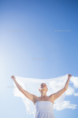 Pretty blonde in white dress holding up shawl on the beachの素材 [FYI00002224]