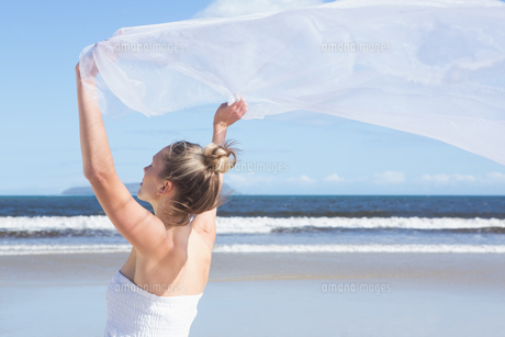 Pretty blonde holding up white shawl on the beachの素材 [FYI00002226]