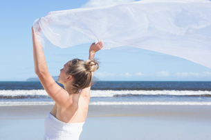 Pretty blonde holding up white shawl on the beachの写真素材 [FYI00002226]