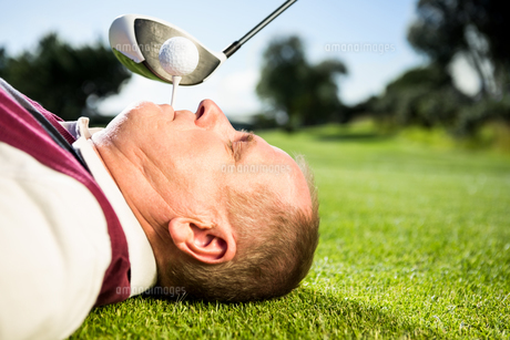Golfer holding tee in his teethの写真素材 [FYI00002227]