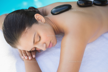 Relaxed brunette lying poolside having a hot stone massageの写真素材 [FYI00002229]