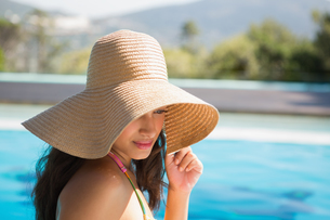 Beautiful brunette sitting by pool wearing straw sunhatの写真素材 [FYI00002231]