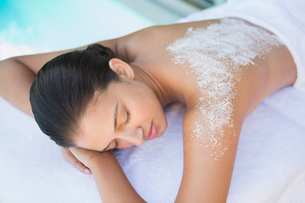 Calm brunette lying on towel with salt treatment on backの素材 [FYI00002233]