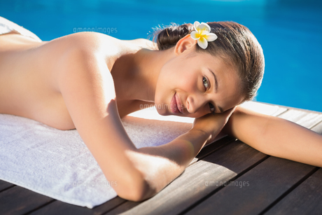 Smiling brunette lying on a towel poolsideの写真素材 [FYI00002234]