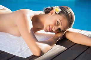 Smiling brunette lying on a towel poolsideの写真素材 [FYI00002234]