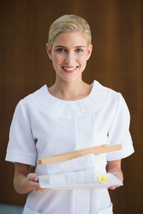 Smiling beauty therapist holding white towelsの写真素材 [FYI00002238]