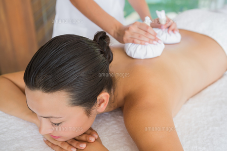 Content brunette getting a herbal compress massageの素材 [FYI00002242]