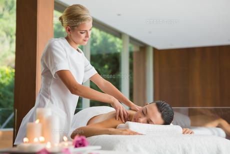 Smiling brunette getting a shoulder massageの写真素材 [FYI00002244]