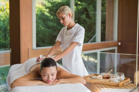 Content brunette enjoying a herbal compress massageの素材 [FYI00002245]