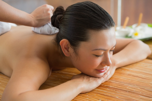 Smiling brunette getting a herbal compress massageの写真素材 [FYI00002246]