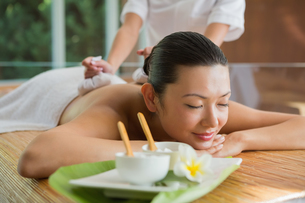 Smiling brunette getting a herbal compress massageの写真素材 [FYI00002248]