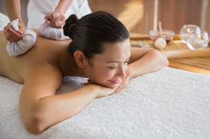 Content brunette enjoying a herbal compress massageの写真素材 [FYI00002251]