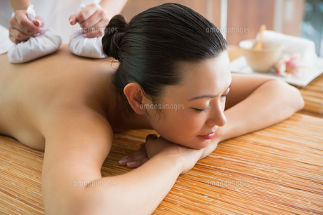 Smiling brunette getting a herbal compress massageの素材 [FYI00002253]