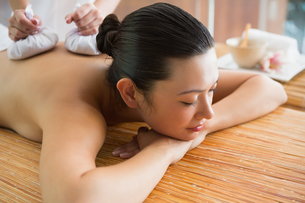 Smiling brunette getting a herbal compress massageの写真素材 [FYI00002253]
